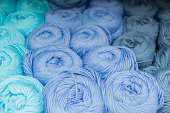 Close-up of skeins of thread in turquoise, blue and grey pastel colors. Thread background.