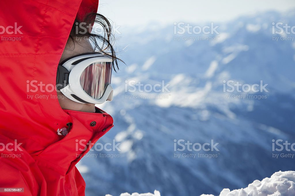 Close-up of skiing girl with goggles, on mountains background stock photo