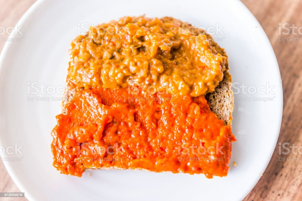 Closeup of slice piece of whole wheat sprouted toasted grain bread on plate with orange red bell pepper vegetable eggplant spread on table macro flat top down view stock photo