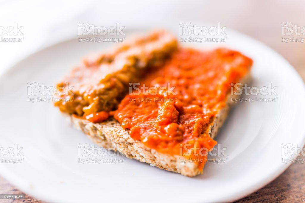 Closeup of slice piece of whole wheat sprouted toasted grain bread on plate with orange red bell pepper vegetable eggplant spread on table macro stock photo