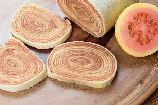 Closeup of slices of roll cake (bolo de rolo) next to guavas on a wooden board.