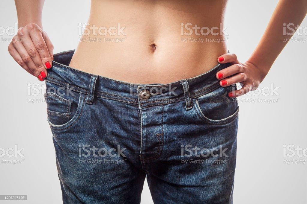 Nahaufnahme der schlanke Taille der jungen Frau im großen Jeans und grauen Top zeigt erfolgreiche Gewichtsabnahme – Foto