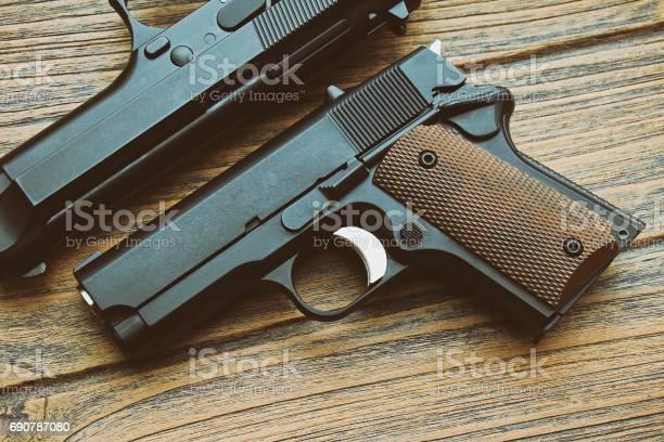 Close-up of small black gun (compact handgun) lying on wooden background, .45 pistol, Women gun.