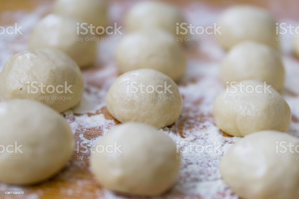 A close-up of small, white balls of home-made dough for a multi-layered banitsa and pizza on a kitchen table, flour for kneading. Shallow depth of focus. stock photo