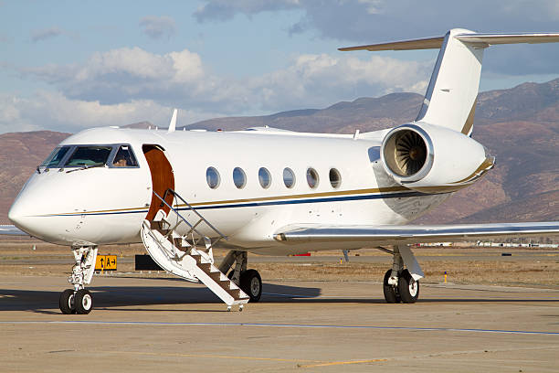 Close-up of small white corporate jet parking in airport stock photo