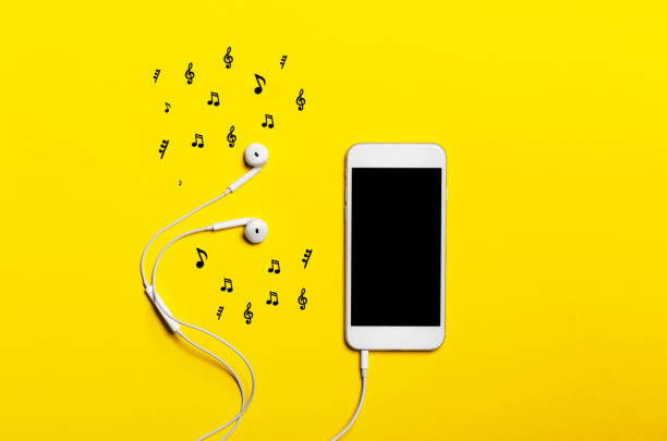 黄色の背景の上にヘッドフォンを持つスマート フォンのクローズ アップ。(上面図)。音楽に耳を傾けます。 ストックフォト
