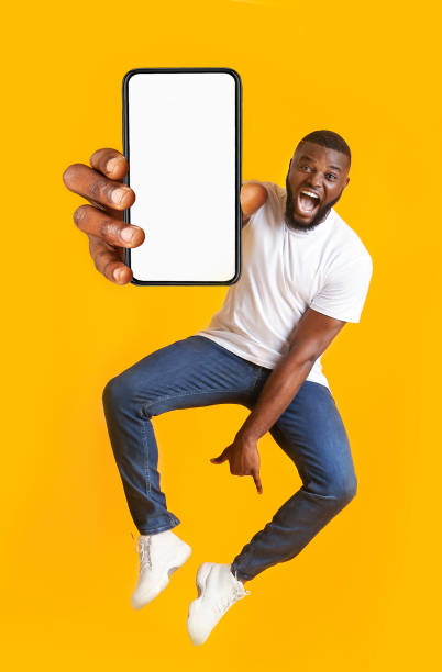 Closeup of smartphone with blank screen in black guy hand stock photo