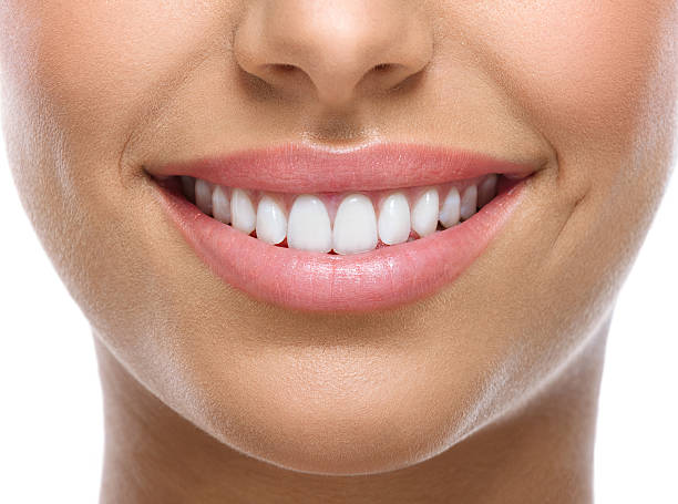closeup of smile with white teeth - teeth stock photos and pictures