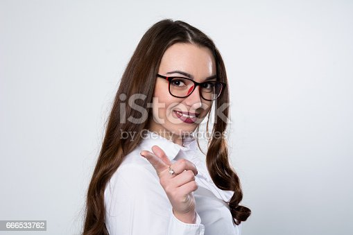 620404536istockphoto Close-up of smiling business woman pointing finger 666533762