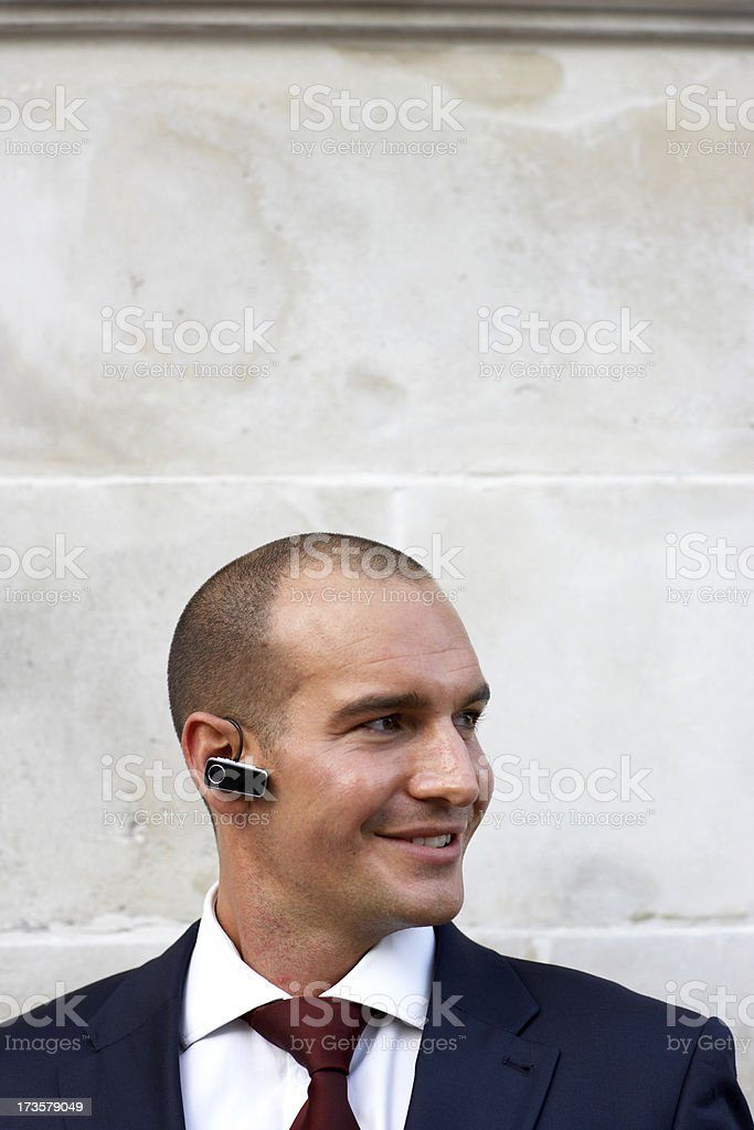 Close-up of smiling businessman using bluetooth earpiece royalty-free stock photo