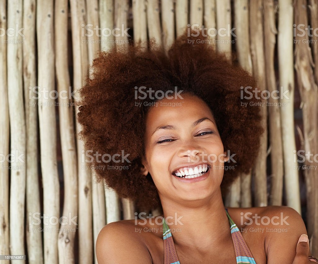 Closeup of smiling cute female against a bamboo wall royalty-free stock photo