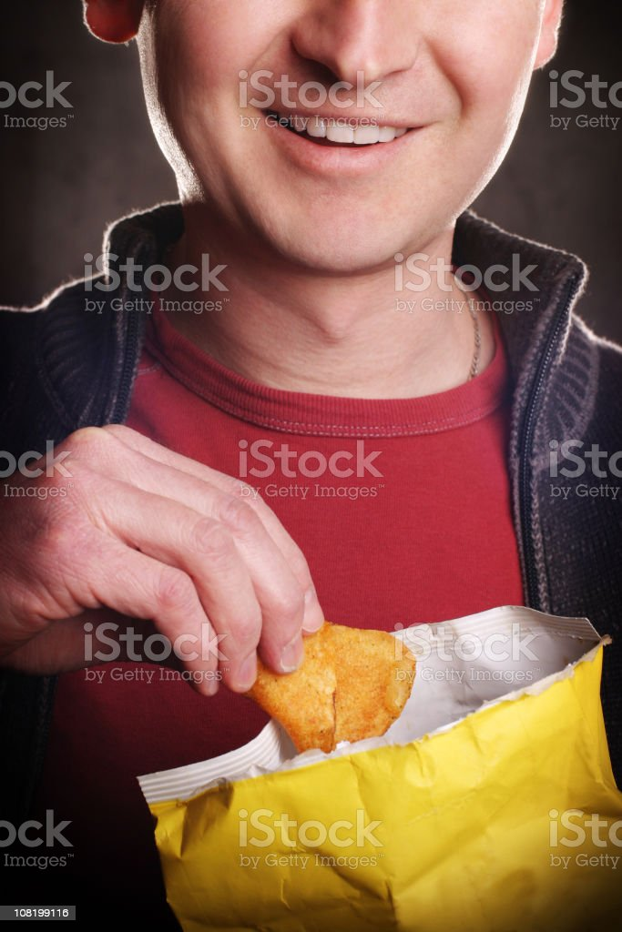 Close-up of Smiling Man Eating Potato Chips stock photo