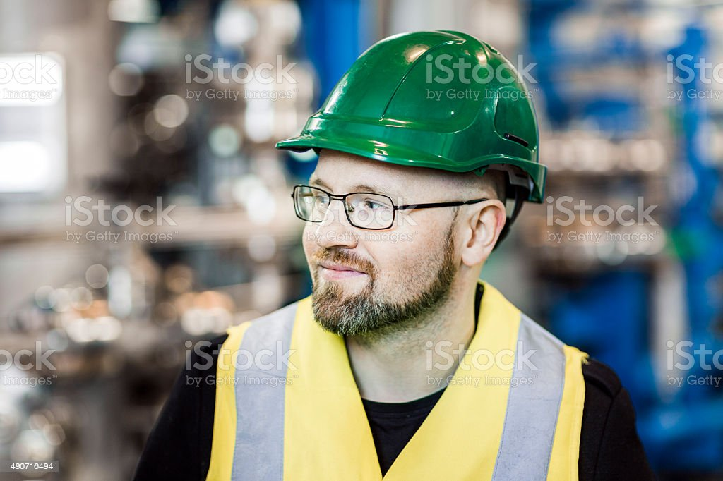 Close-up of smiling manual worker looking away in factory stock photo