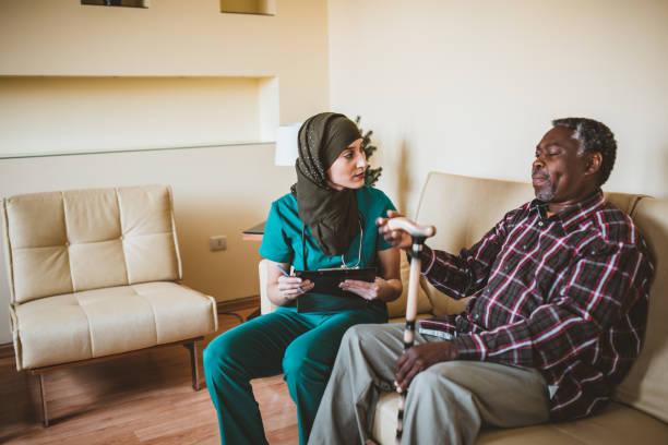 Plan rapproché de l'homme aîné de sourire avec le bâton de marche et l'infirmière amicale. Aide-soignant amical parlant avec un vieil homme heureux avec un bâton de marche à un sanatorium. Une femme musulmane docteur et son patient afro-américain a - Photo
