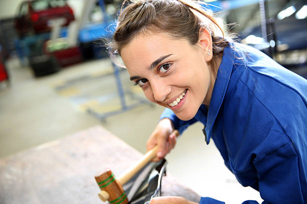 Closeup of smiling student in auto shop with mallet stock photo