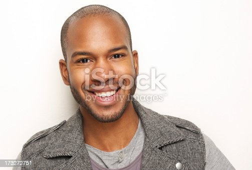 Close-up portrait of a handsome young black man smiling against white background
