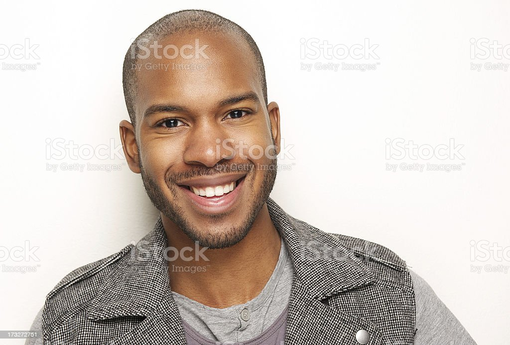 Close-up of smiling young, dark-skinned man stock photo