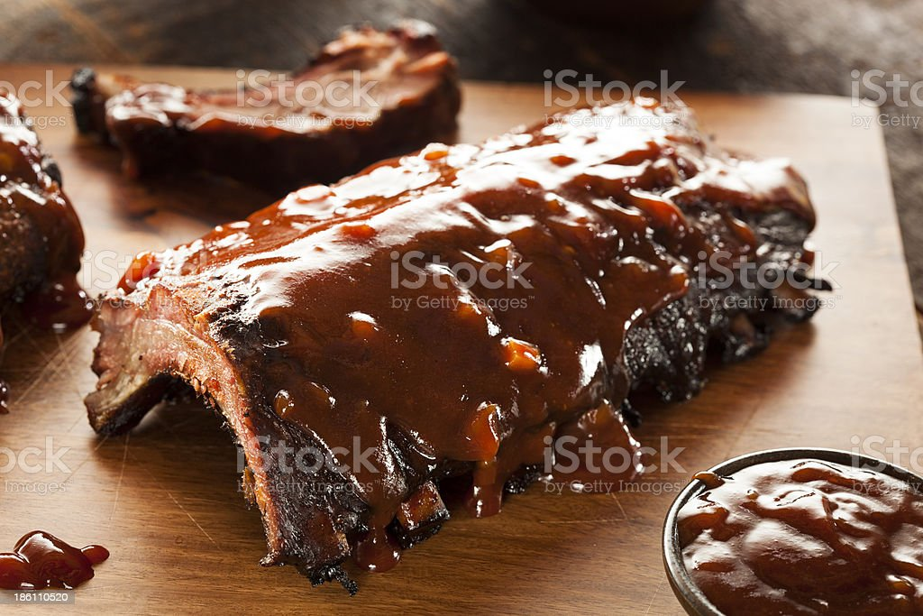 A close-up of smoked barbecue pork spare ribs on wood stock photo
