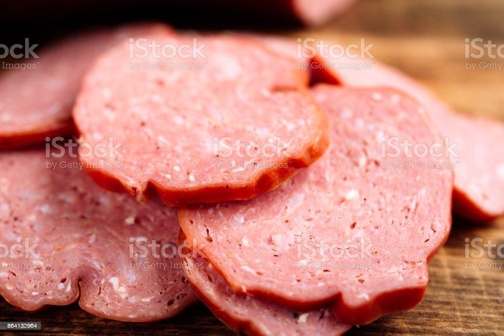 Closeup of smoked sausage on cutting board royalty-free stock photo