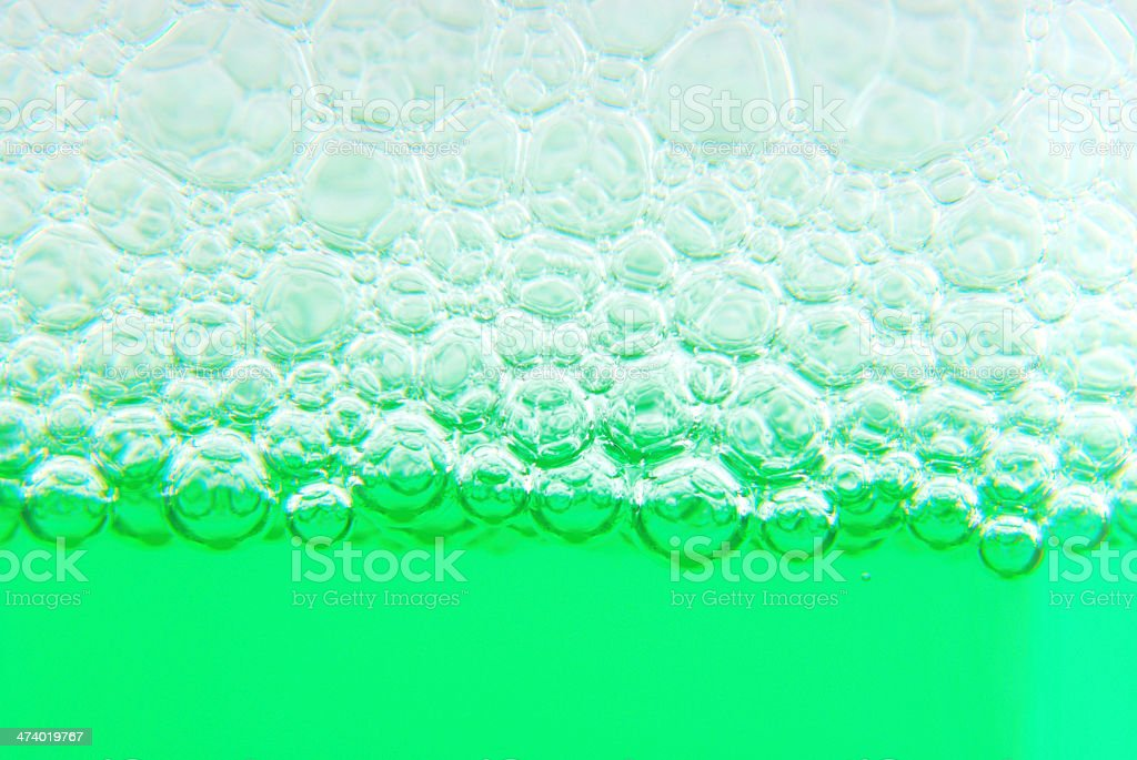 Close-up of soap bubble suds in green water royalty-free stock photo