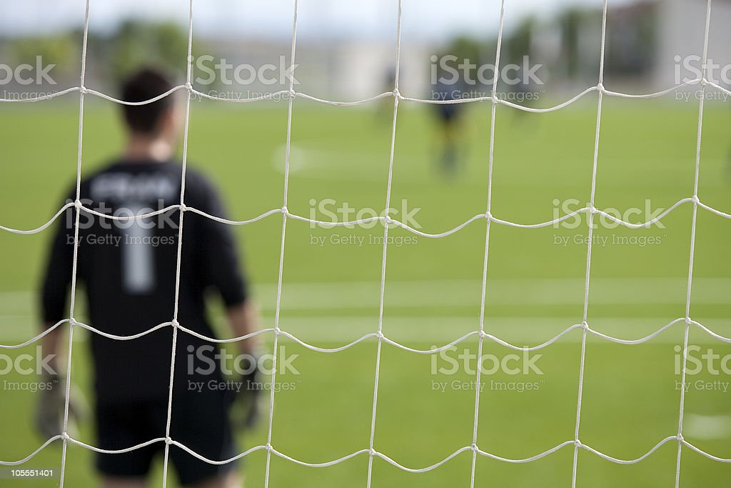 Close-up of soccer goal with player in the background stock photo