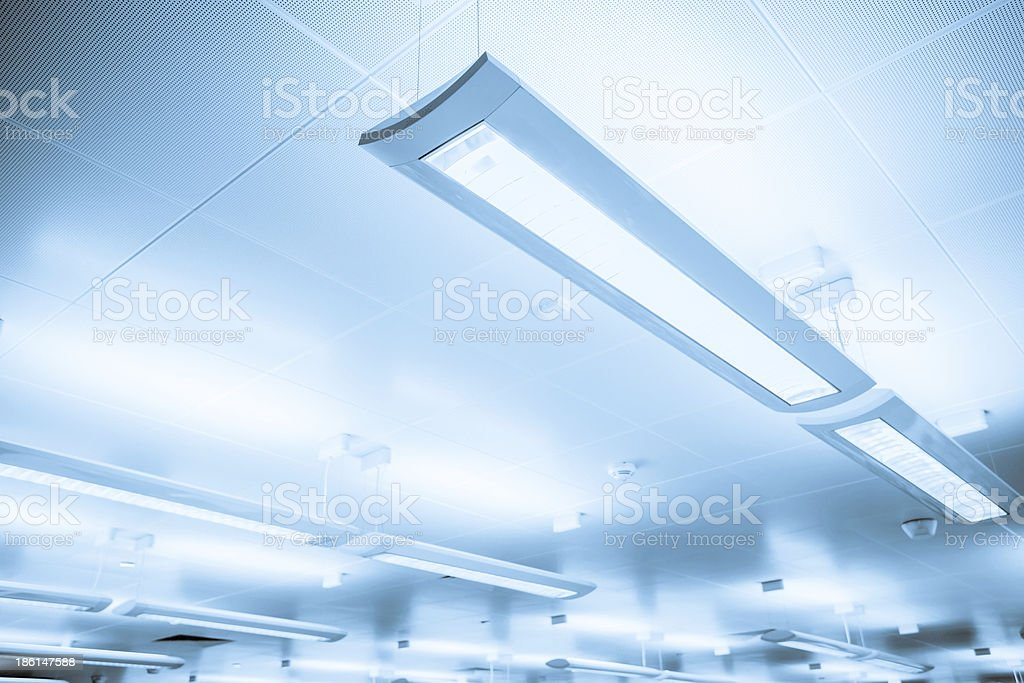 Close-up of some indoor lighting bars hanging from ceiling stock photo