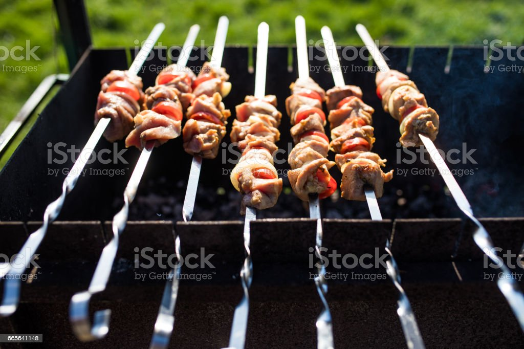 closeup of some meat skewers being grilled in a barbecue. Outdoors stock photo