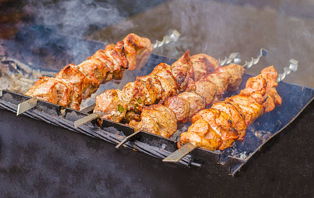 closeup of some meat skewers being grilled in a barbecue. - ムーア様式 ストックフォトと画像