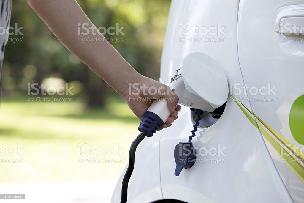 Close-up of someone's arm charging a white electric car stock photo