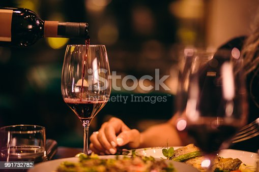 Close-up of waiter holding bottle and serving red wine during dinner at luxurious gourmet restaurant