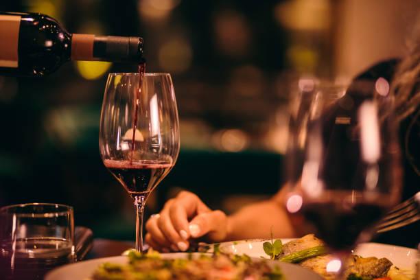 primer plano de sumiller sirviendo vino tinto en el restaurante - restaurante fotografías e imágenes de stock