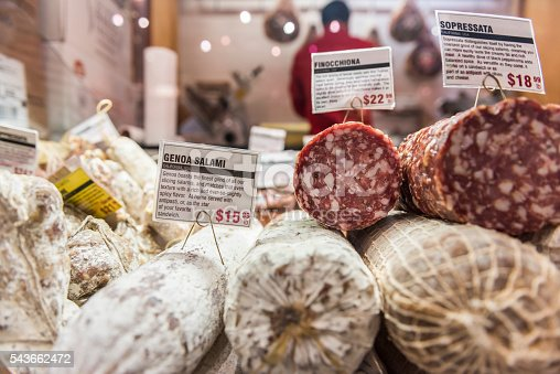 Closeup of sopressata and genoa salami rolls on display in a market shop with butcher in background