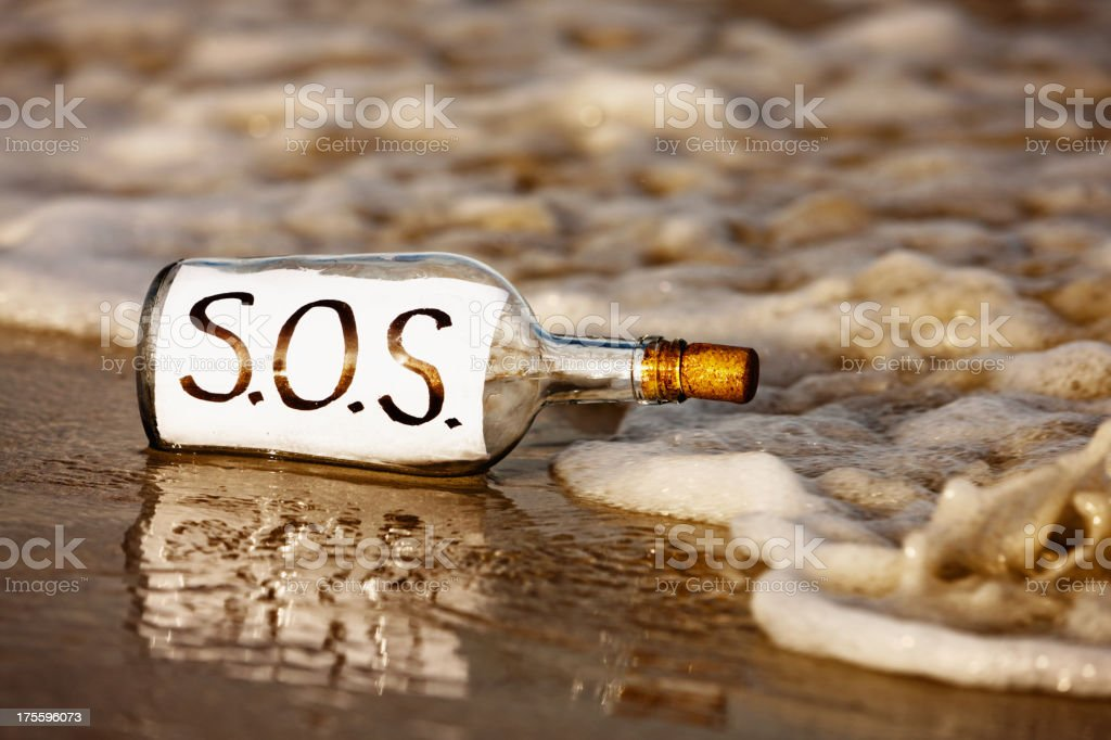 Close-up of SOS message in bottle at shoreline royalty-free stock photo