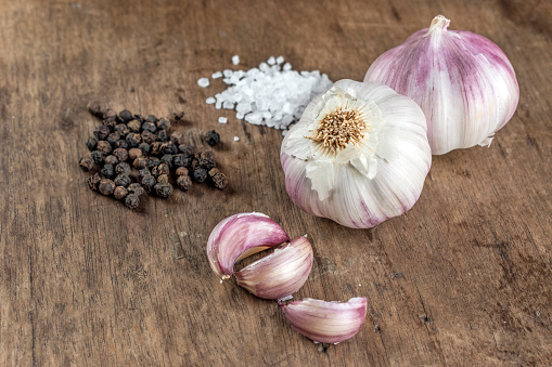 Closeup of spices, showing purple whole garlic bulbs, garlic cloves, black pepper and white salt, on top of a wooden surface, 45 degrees angle view.