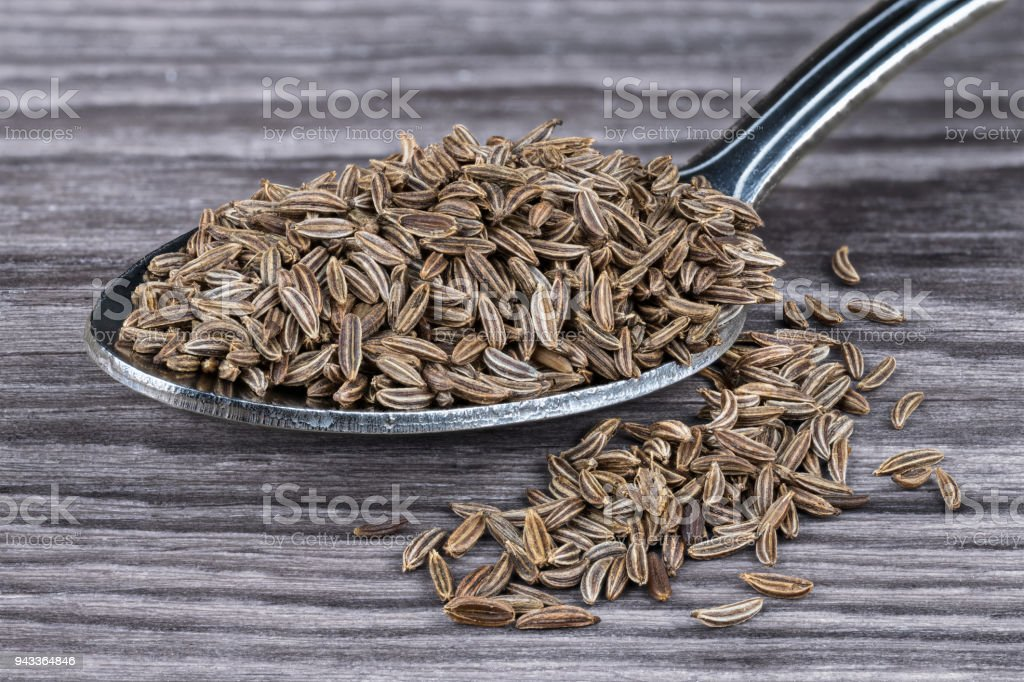Close-up of spoonful of aromatic caraways on wood. Carum carvi stock photo