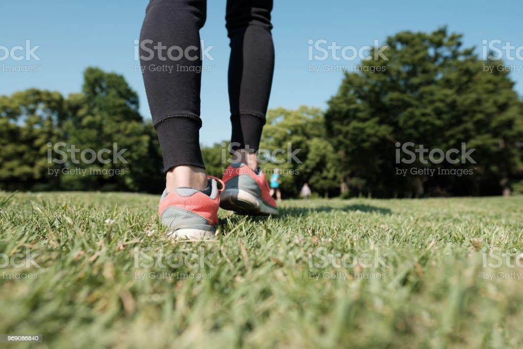 草の上を歩くスポーツの靴のクローズ アップ ストックフォト