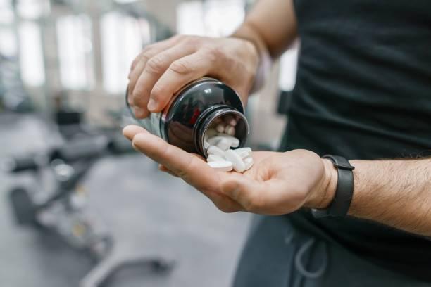 Primer plano de los brazos de hombre musculoso deportivo mostrando deportes y fitness suplementos, CAPSULAS, pastillas, gimnasio fondo. Estilo de vida saludable, medicina, suplementos nutricionales y el concepto de personas - foto de stock