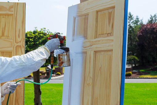 istock Close-up of spray gun with paint painting Master painting wood doors. 1042836232