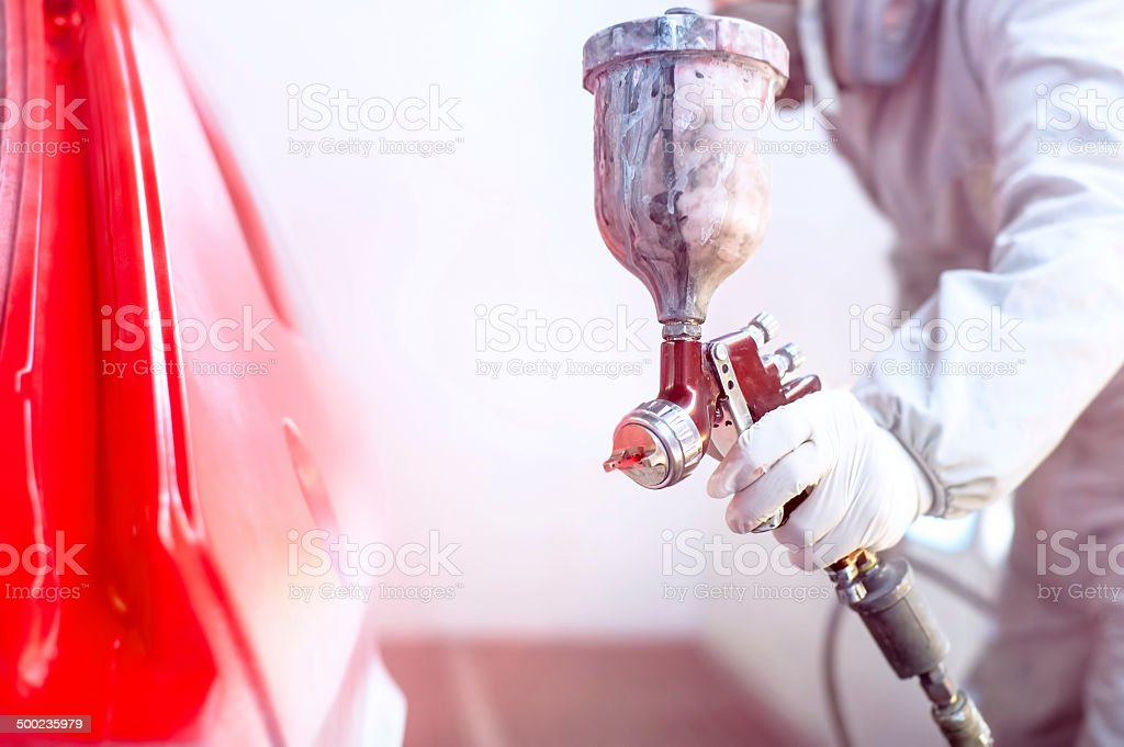 Close-up of spray gun with red paint painting a car stock photo