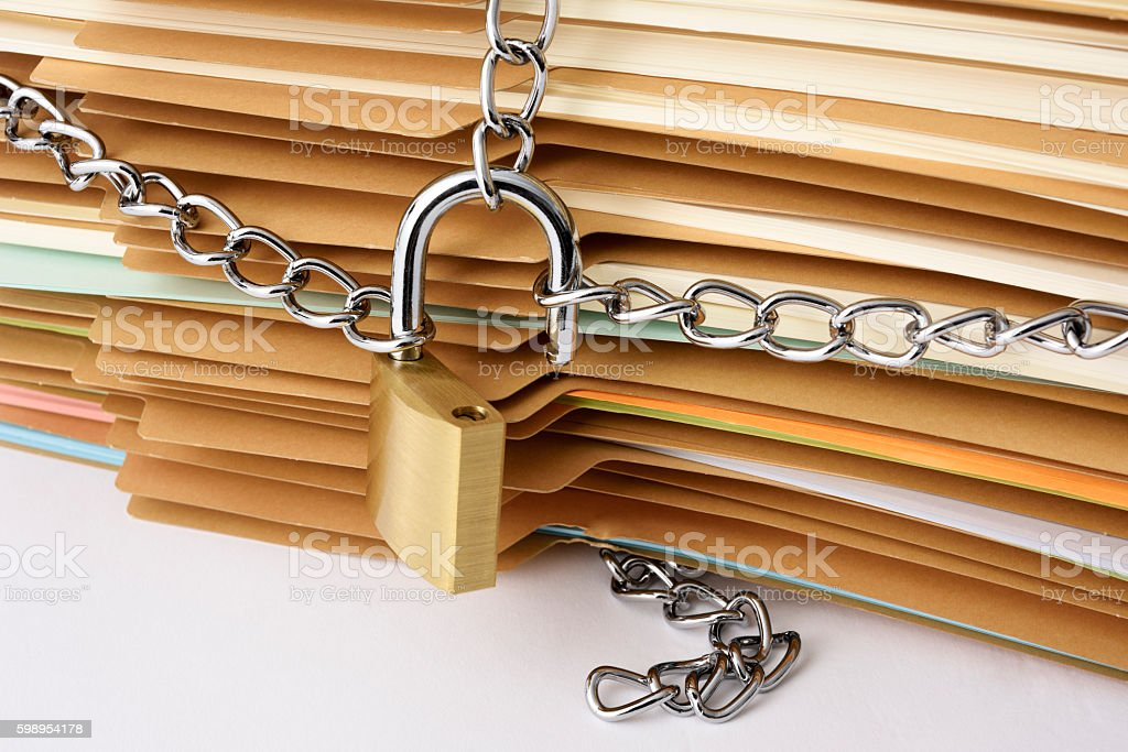 Close-up of stacked brown file folder with unlocked padlock stock photo
