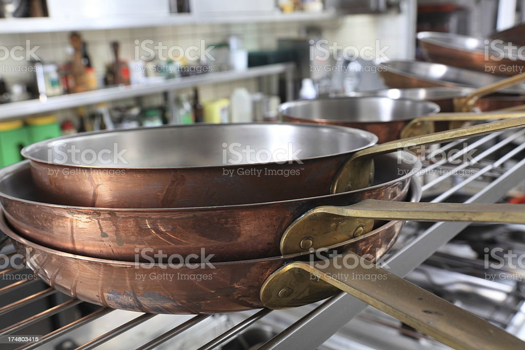 closeup of stacked copper fryingpans in a professional kitchen stock photo