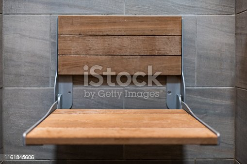 487881729 istock photo Closeup of staging modern stone grey tiled bathroom in apartment or house with closeup of wooden seat in shower 1161845606