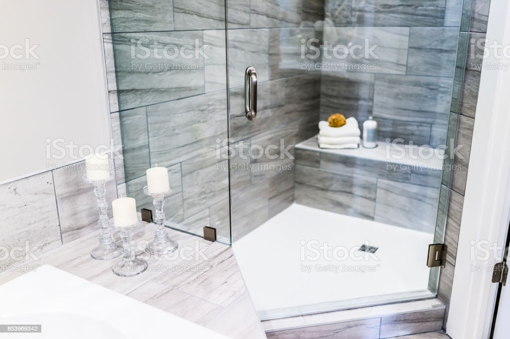 Closeup of staging modern stone grey tiled bathroom, marble countertop in model home, apartment or house with candles, towels, pouf, soap dispenser, glass shower door stock photo