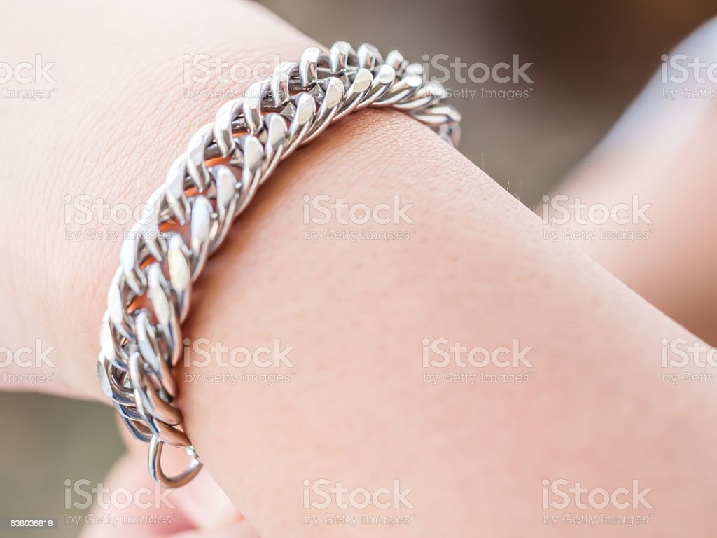 Closeup of stainless steel bracelet and girl hand stock photo