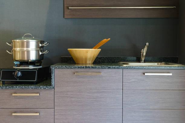 nahaufnahme der edelstahl kochtopf auf induktionskochfeld in zeitgenössischen modernen küche zu hause. - griffe für küchenschränke stock-fotos und bilder