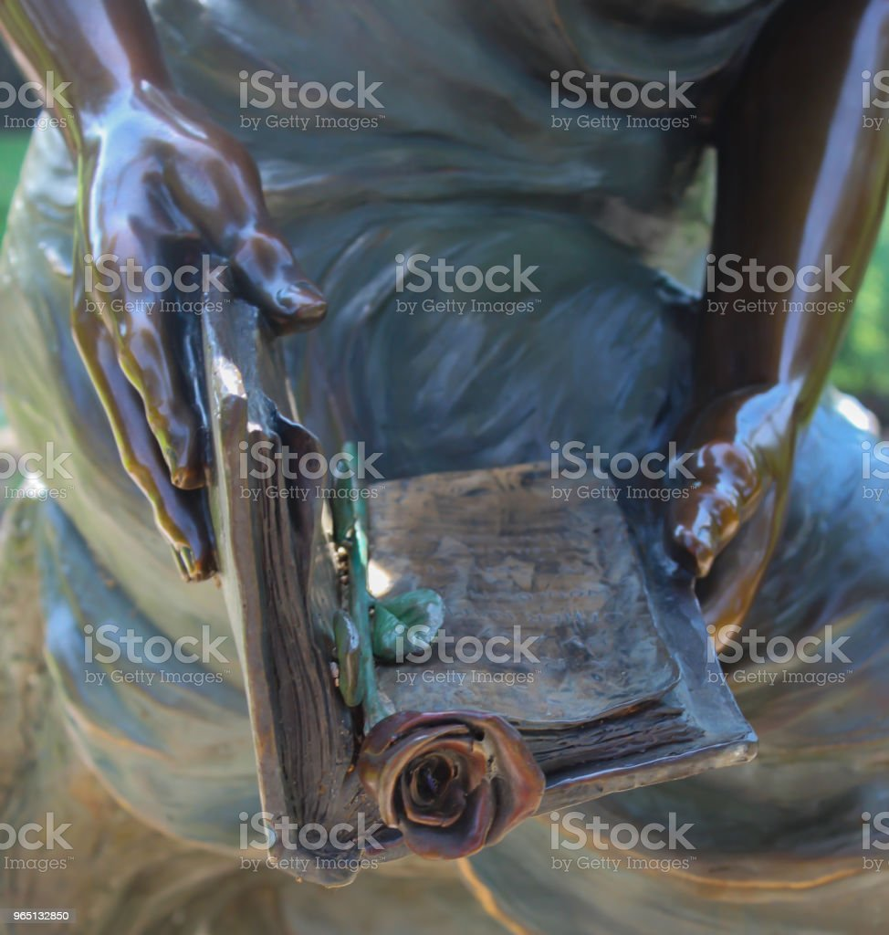 Closeup of statue hands holding book bookmarked with a rose zbiór zdjęć royalty-free