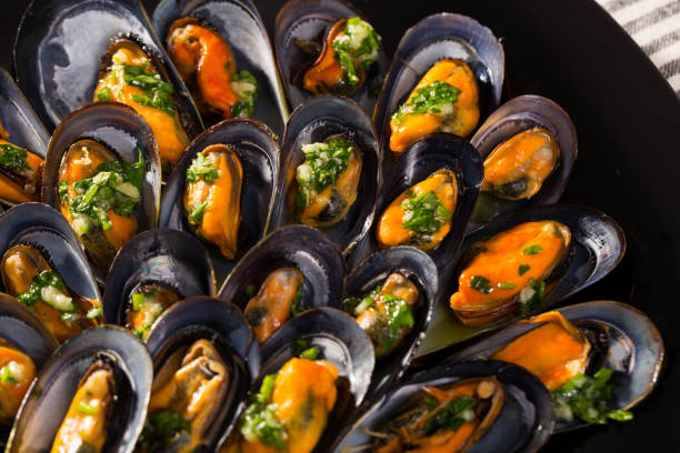 Closeup of steamed mussels on black dish Closeup of appetizing steamed mussels with sauce of oil, garlic and parsley on black ceramic dish mussel stock pictures, royalty-free photos & images