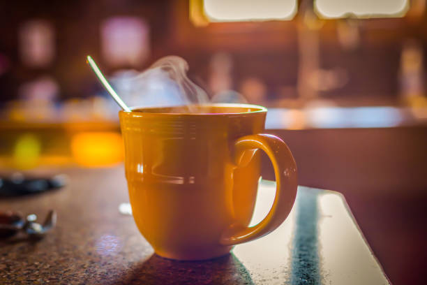 closeup of steaming cup of coffe in morning light - selective focus stock photos and pictures