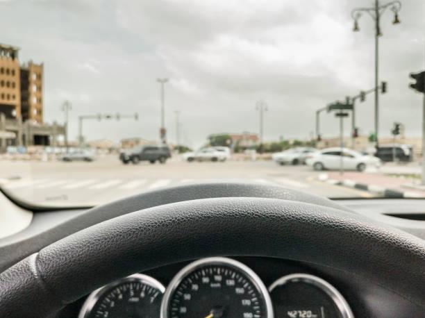 nahaufnahme der lenkung eines langsam beschleunigenden autos und verschwommener hintergrund eines noblen bereichs einer modernen stadt in den frühen morgenstunden - auto trennwand stock-fotos und bilder
