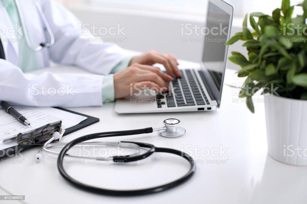 Close-up do estetoscópio é deitada na mesa perto médico feminino digitando no computador portátil - foto de acervo